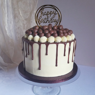 Buttercream birthday cake with chocolate drip decorated with chocolate balls