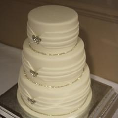 3 tier cake with fondant ribbon, diamante heart brooches and diamante trim