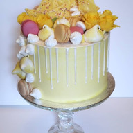 Yellow themed buttercream birthday cake with drip effect, chocolate bark, meringues, macarons and fresh flowers