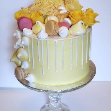 Yellow themed buttercream birthday cake with drip effect, chocolate bark, meringues, macarons and fresh flowers