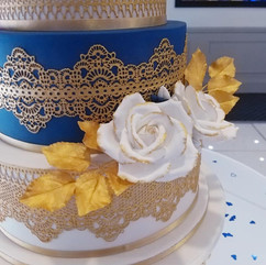 White sugar roses edged in gold, with gold leaves and gold edible lace.