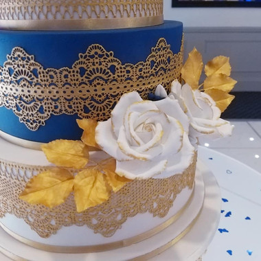 Sugar rose detail on blue, white and gold wedding cake