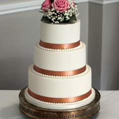 3 tier wedding cake with rose gold ribbon, fondant pearls and fresh flowers