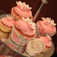 Wedding cupcakes decorated with a swirl of buttercream and fondant flowers.