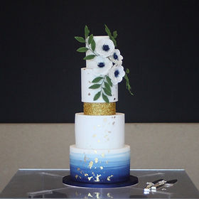 Four tier navy blue and white wedding cake decorated with gold leaf, gold glitter, sugar flowers and leaves