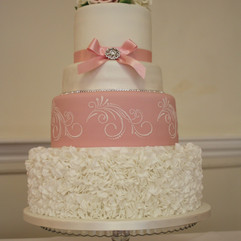 4 tier cake with fondant ruffles, stencilled designs and sugar roses topper