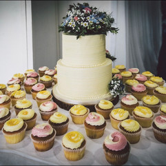 2 tier buttercream wedding cake with fresh flowers and cupcakes