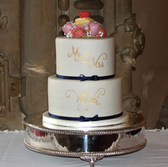 2 tier wedding cake with gold writing, sugar tulip and ranunculus topper