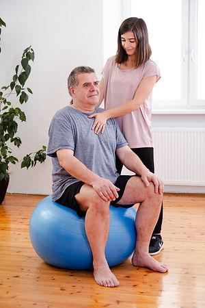 Physiotherapeutin am Arbeiten mit Patient am Gymnastikball