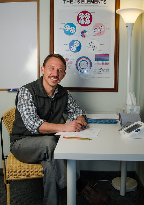 David Konikowski sitting at a desk in Four Corners Chinese Medicine