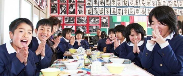 "Students siting ""Itadakimasu"" before school lunch."
