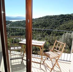 Balcón con mesa y sillas y vistas al lago