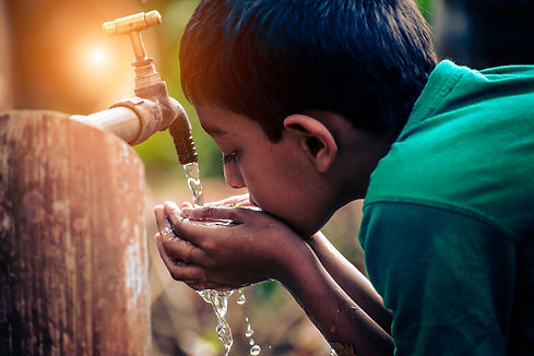 Young rural Indian boy drinking clean water from a tap