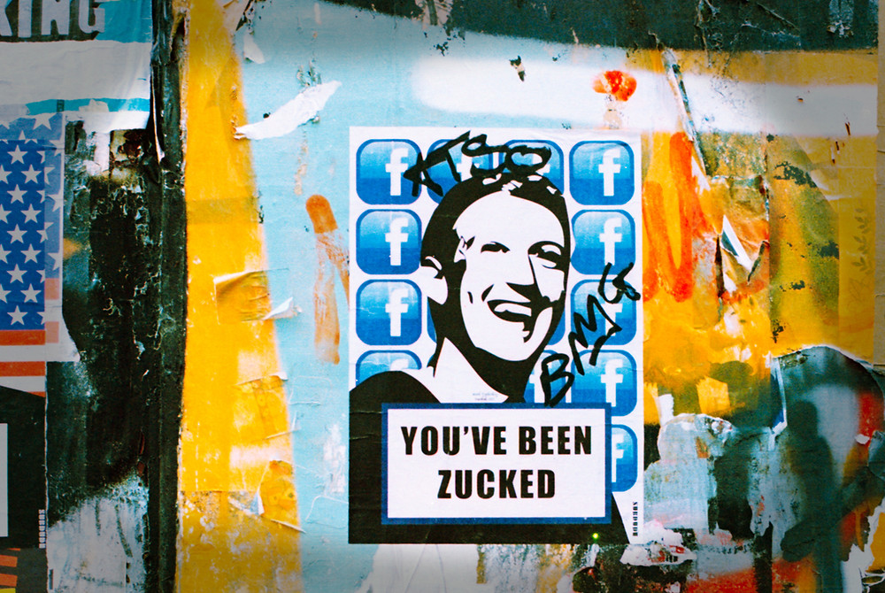 A protest street poster with a portrait of a laughing Mark Zuckerberg and facebook icons with the words: You've Been Zucked.