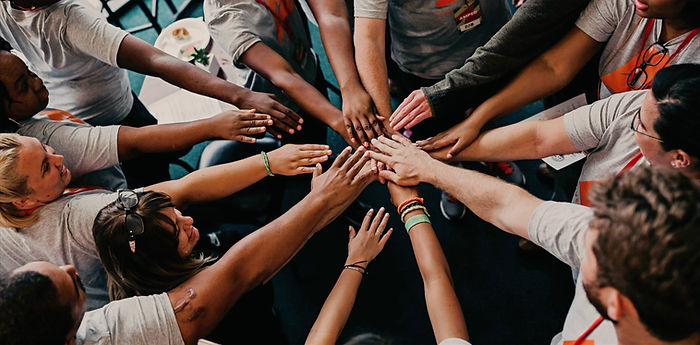 A multi racial group in a handle huddle photo by Camylla Battani on unsplash.com