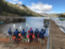 Six young men holding oars in front of kayaks looking out to a lake