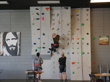 Teen climbing while being belayed