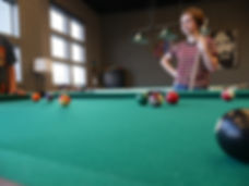 Teen girl holding pool stick behind pool table