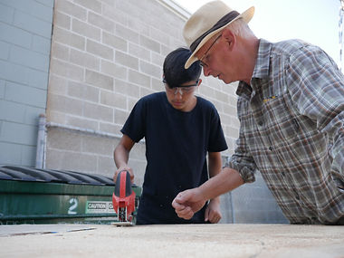 Instructor teaching student how to use a power saw