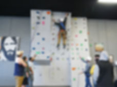 Climber climbing indoor rock wall and cheered on by crowd