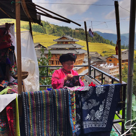 Woman weaving traditional rugs and clothing.  Million stairs to Longsheng Rice Terraces.