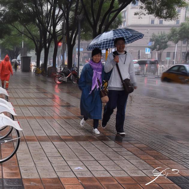 Walking in a heavy rain.  Beijing.