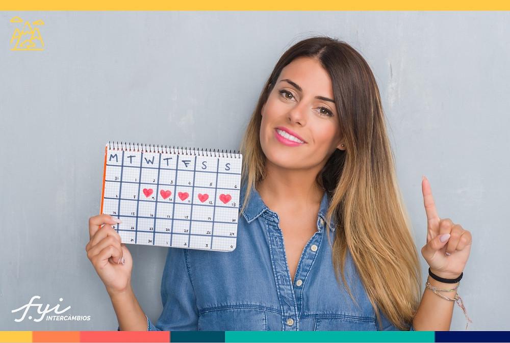 mulher segurando um calendário com o dedo apontando para cima