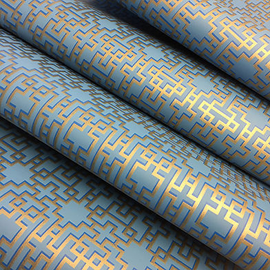 rolls of beautiful wallpaper, with a shimmering gold design, with a dark blue shadow print.