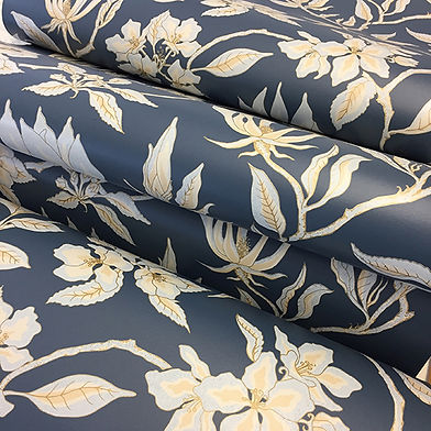 Rolls of wallpaper with a magnolia and apple blossom design. The background of the paper is a stiffkey blue colour and the design is in gold, with subtle pinks
