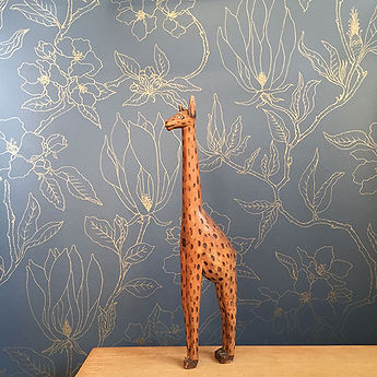 Giraffe in front of navy and gold handprinted wallpaper with designs of magnolia and apple blossoms