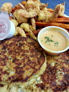 Our Hecksher Drive crab cakes are made fresh, in house with real crab meat! Shown with fried shrimp, sweet potato fries, and Junior's signature Paradise Sauce!