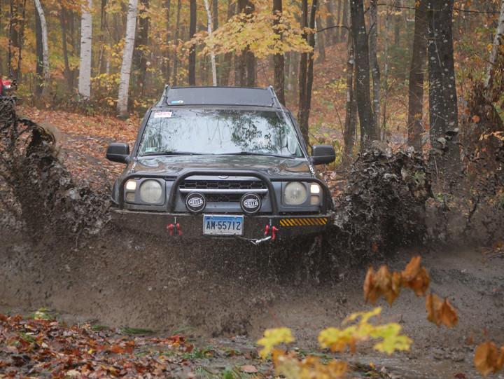 2002 Xterra splashes through mud puddle.