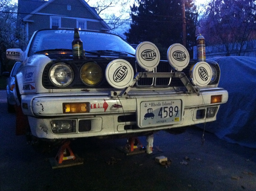 E30 BMW being worked on in driveway.