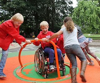 Szőke hajú kerekesszéket használó kisfiú sima gyerekekkel játszik egy inkluzív játszótéri játékon