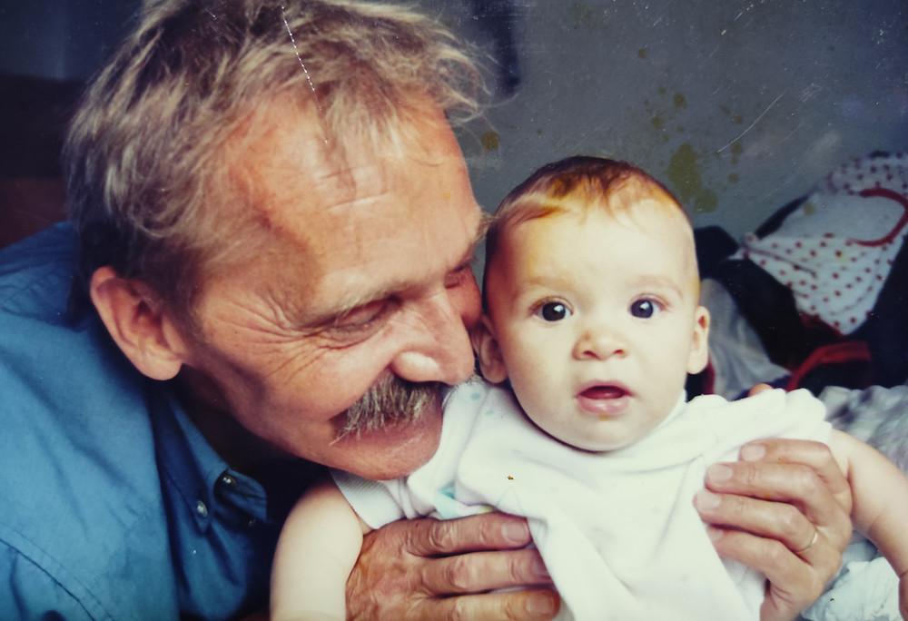 Kékinges, világos hajú, bajuszos férfi egy fehérbe öltöztetett kisbabát tart a kezében és mosolyog rá.