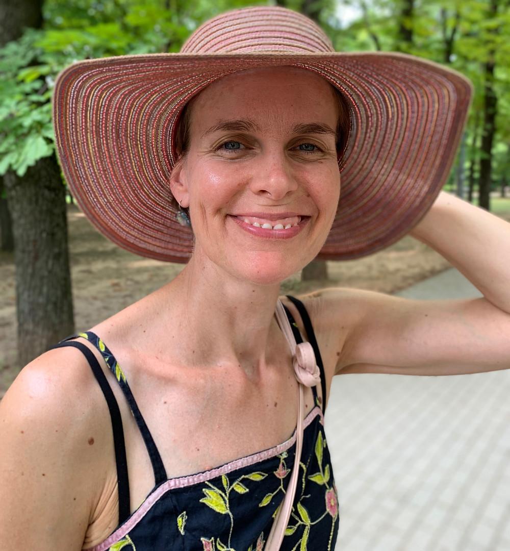 Mosolygó nő, fekete alapon virágos nyári ruhában, fején szalmakalappal, a háttérben zöld falombok