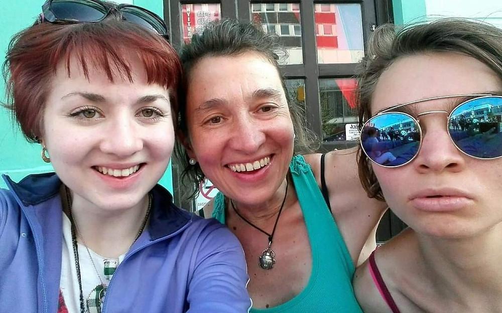 Három rövidhajú nő átkarolja egymást, a baloldali lila pulóverben van és vörös hajára fel van tolva a napszemüveg. A középső idősebb, haja hátra van kötve, nyakában fém medál fekete madzagon, világos türkiz ujjatlan pólóban van. A jobboldalon megint fiatal lány, napszemüvegében emberek tükröződnek.