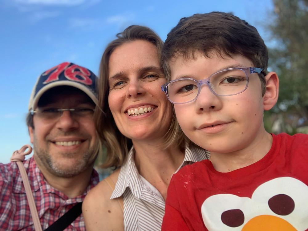 Három mosolygó ember: jobb oldalon előtérben barnahajú szemüveges kisfiú piros pólóban, mögötte világosbarna, rövid hajú nő ujjatlan csíkos ingben, baloldalon hátul borostás szemüveges férfi kockás ingben és baseball sapkában