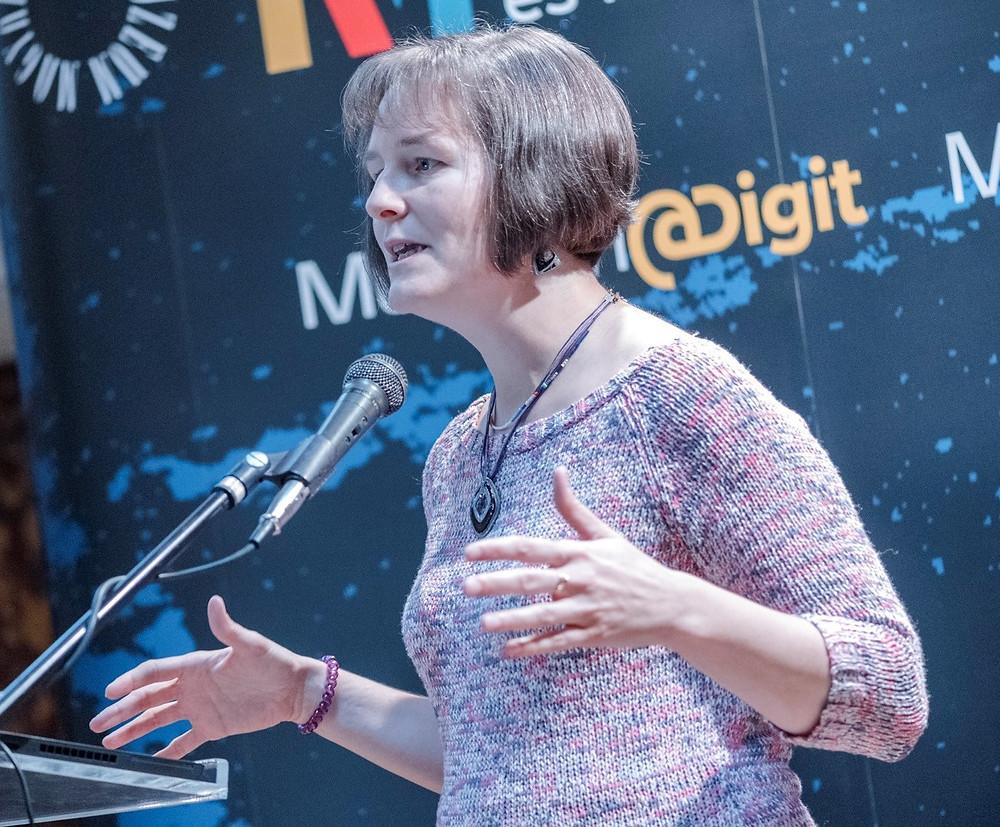 rövidhajú nő kötött pulóverben mikrofonba beszél és kezével gesztikulál