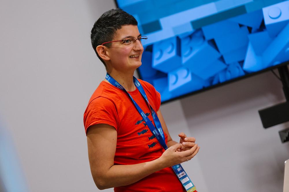 rövid fekete hajú, szemüveges nő piros pólóban egy képernyő előtt áll és mosolyog