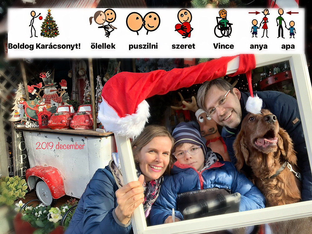 """Egy mikulássapkával díszített képkeretből néz ki rövid, barna hajú nő, tőle jobbra kék kabátban és csíkos sapkában szemüveges kisfiú, jobboldalon pedig borostás szemüveges férfi és egy nagy, hosszúszőrű barna kutya. A háttérben karácsonyi díszek, felül pedig kulcsszavakból és piktogramokból kirakott karácsonyi üzenet: """"Boldog Karácsonyt!, ölellek, puszilni, szeret, Vince, anya, apa. A háttérben baloldalon piros felirat: 2019 december"""
