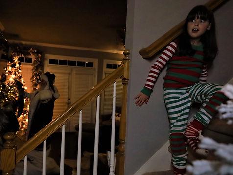 little girl spying on santa delivering christmas presents