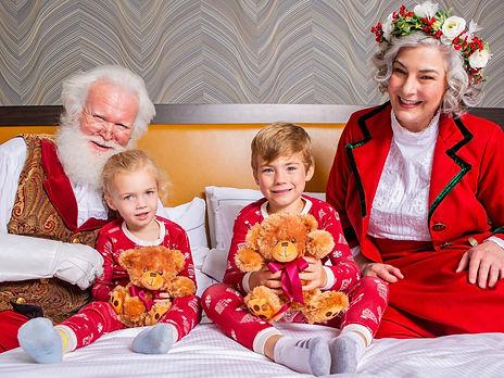 santa tucking kids into bed