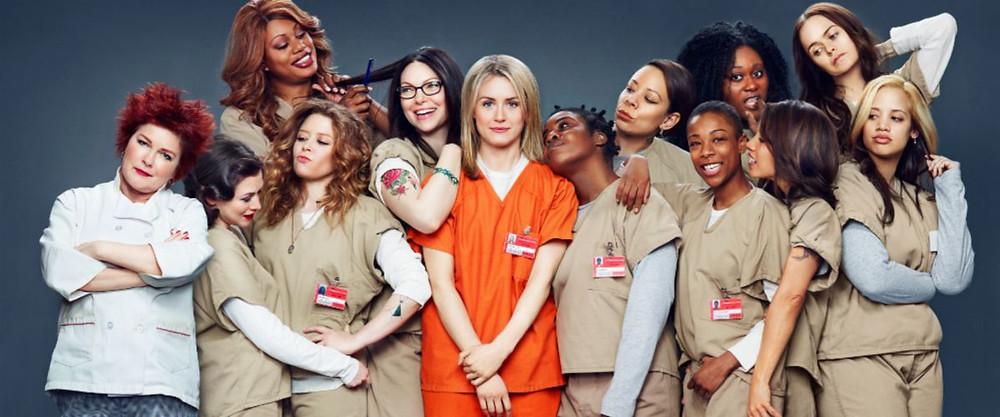 Photo promotionnelle de la série Orange is the new black. 13 femmes en tenue de prison sont représentées.