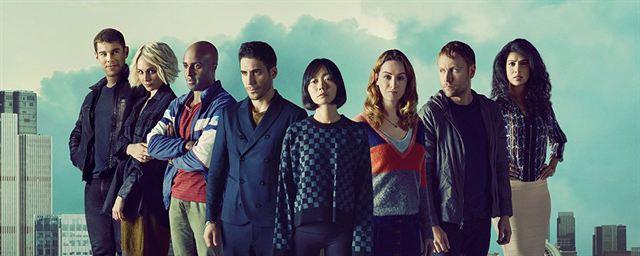 Photo promotionnelle de la série Sense8. 8 personnes se tiennent debout avec un arrière-plan de gratte-ciel.