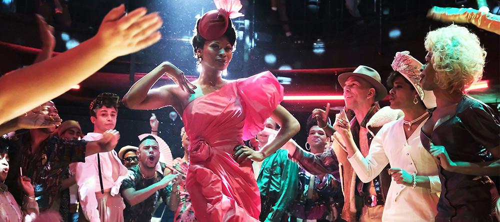 Extrait de la série Pose. Une femme défile en tenue de soirée rose pendant que la foule l'applaudit.