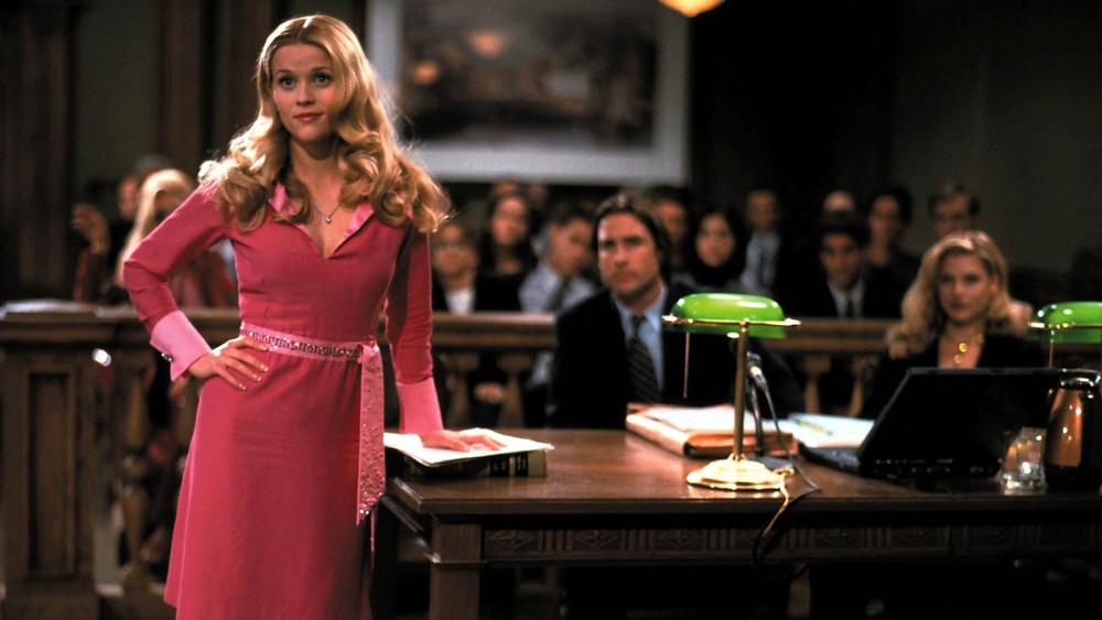 Extrait du film La Revanche d'une blonde. Une femme habillée en rose se tient debout dans un tribunal.