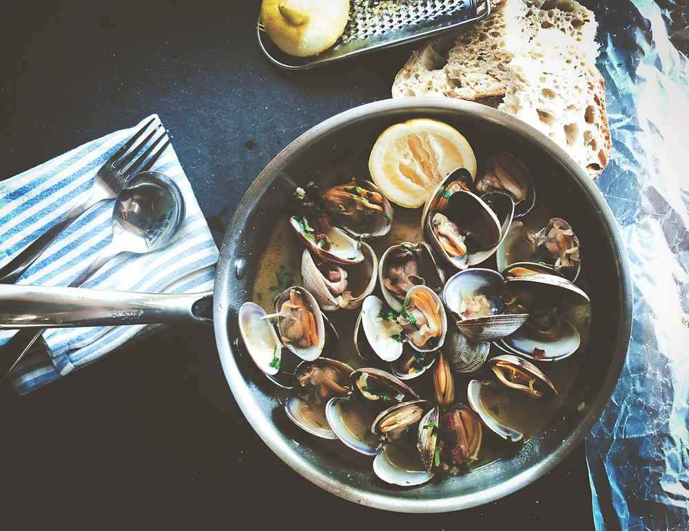 Mussels, small shellfish, cooked in the shell in a saute pan, wedge of lemon and crusty slice of bread are ready for enjoying with the meal.