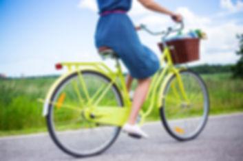 side view of young woman riding retro bi