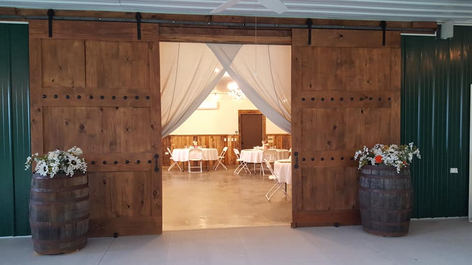 Barn door with barrels and tables and ch